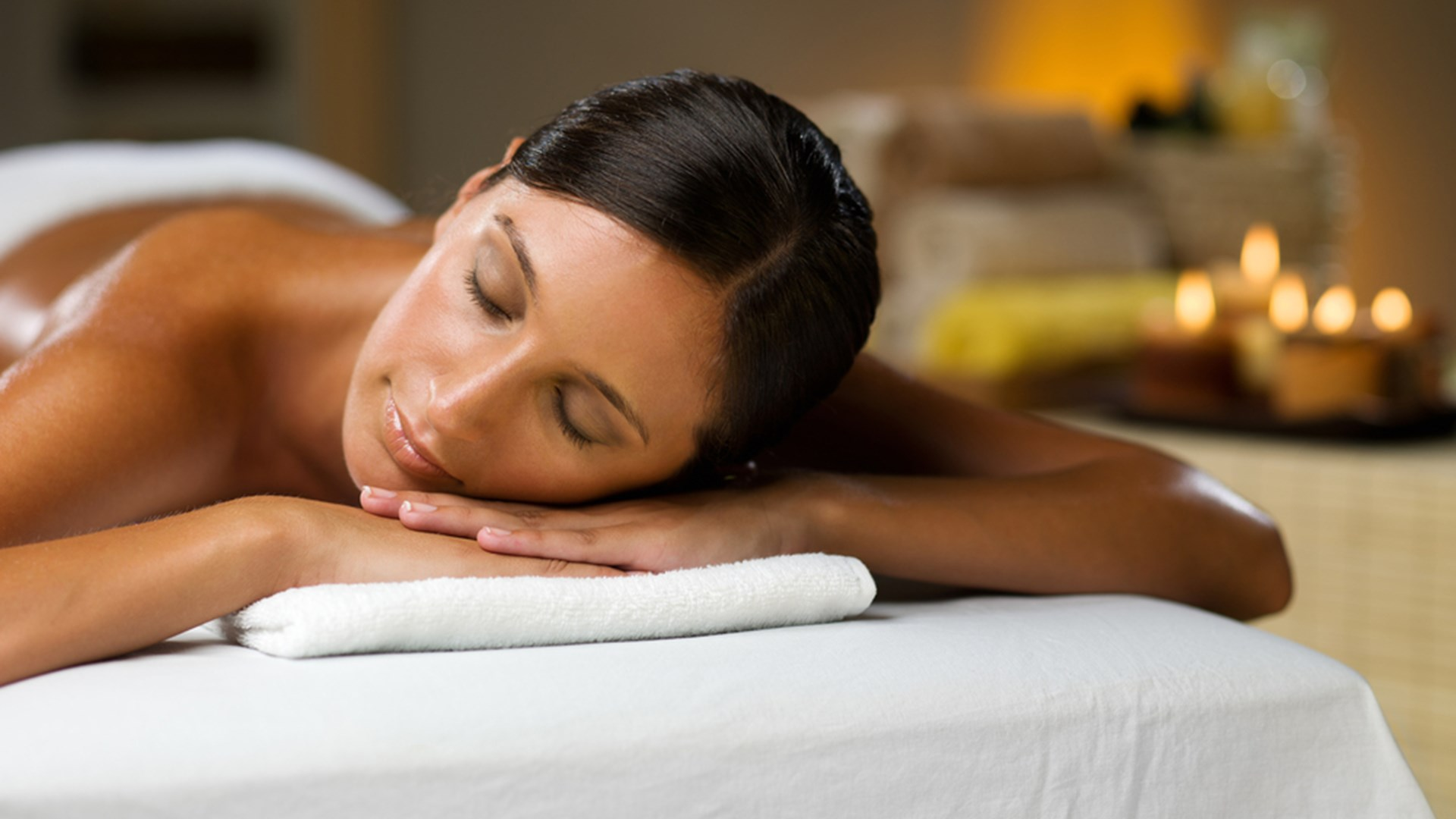 A woman lying on her front on a massage table awaiting her spa treatments