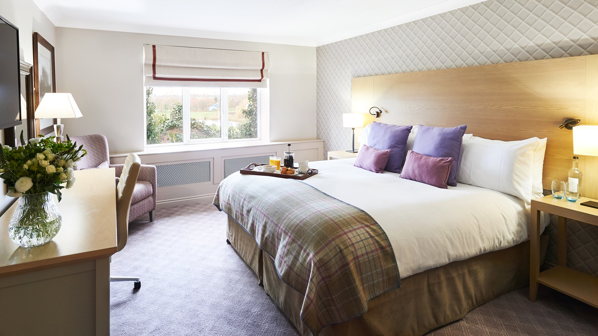 Manor House Suite with large kingsized bed with tartan interiors and wooden furniture and room service