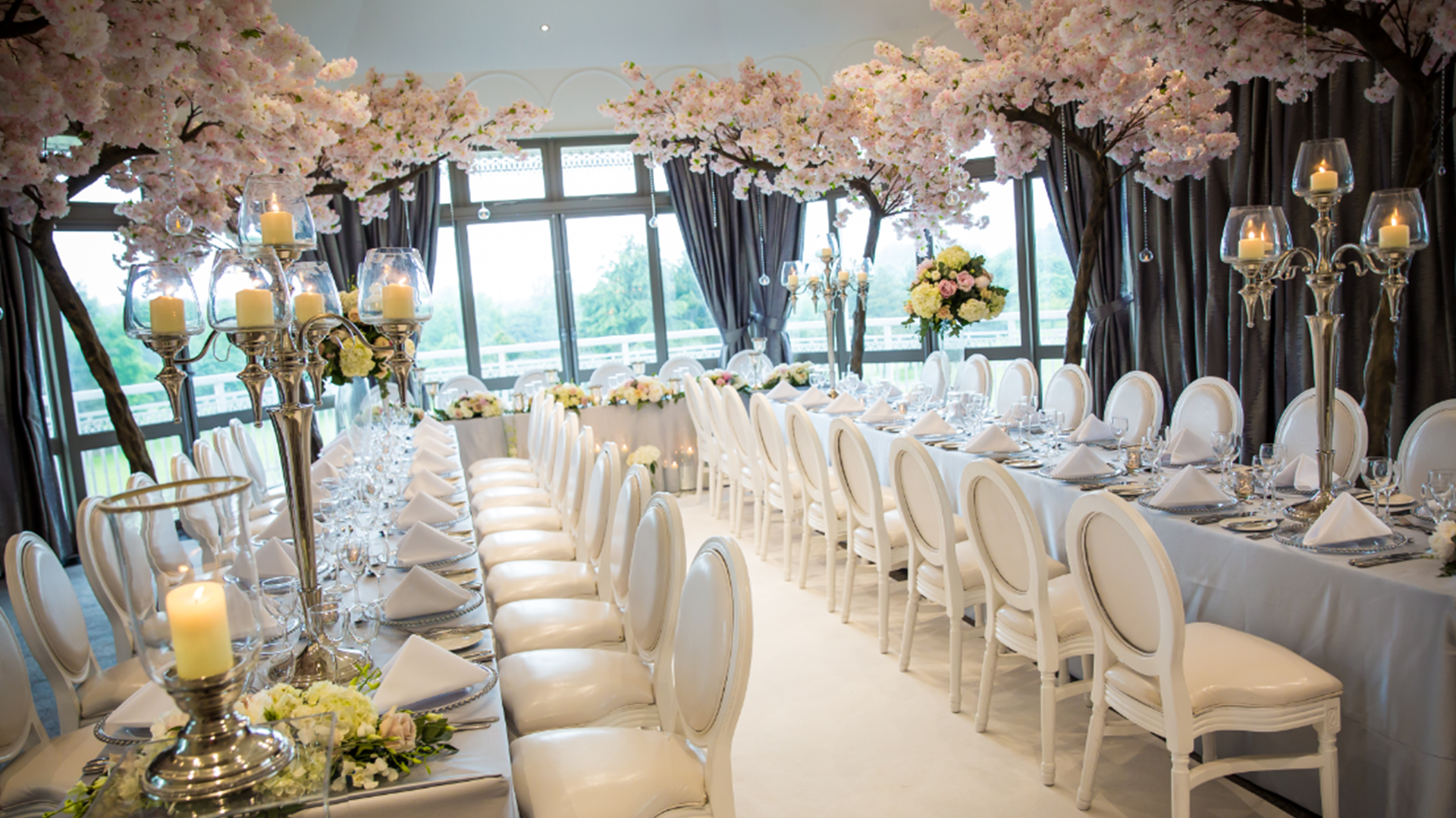 Wedding aisle decorated with floating candles in glass vases and floral arrangements