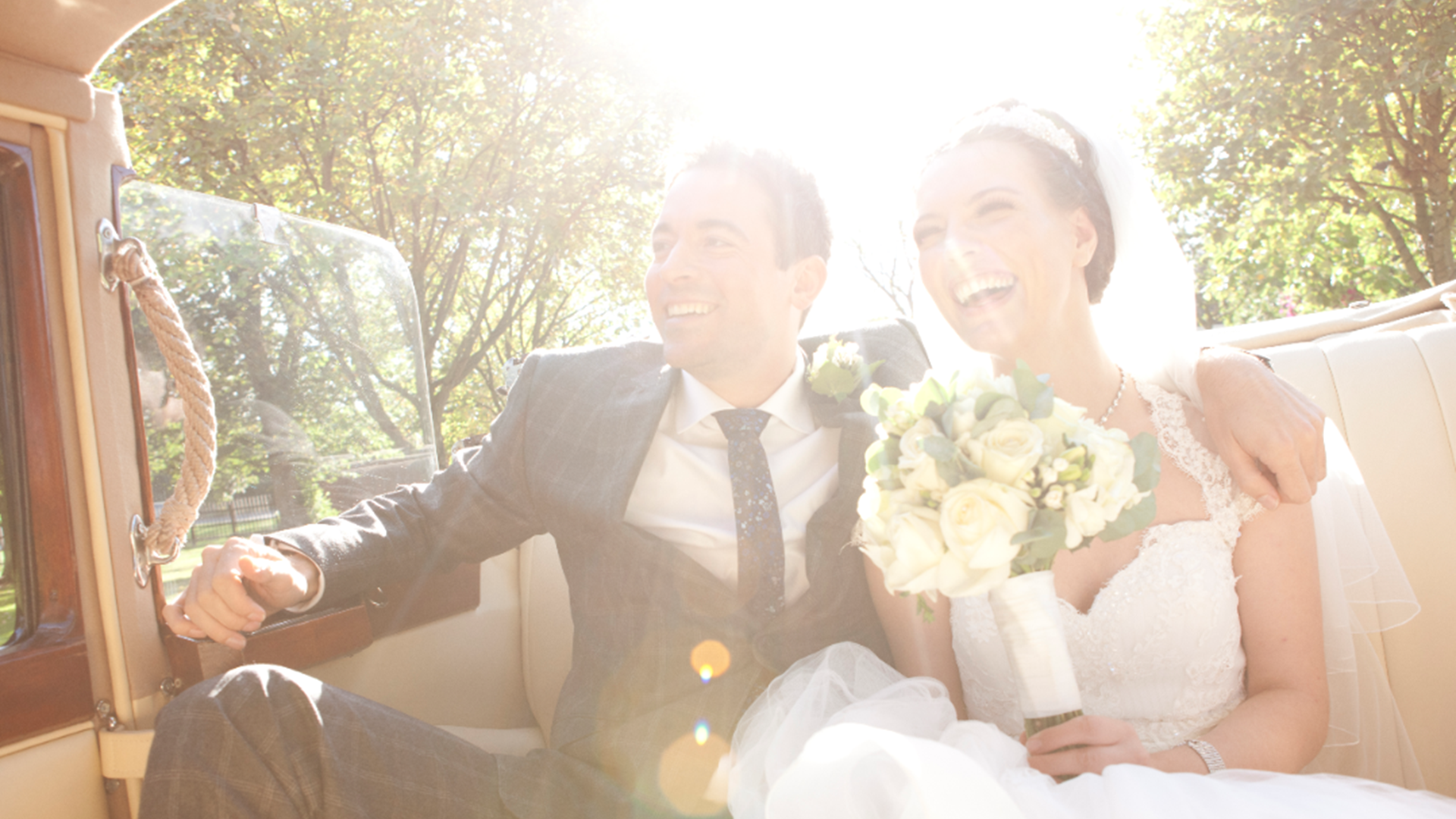Newly married couple laughing and smiling in the back of their wedding car, driving through the trees with the sun shining