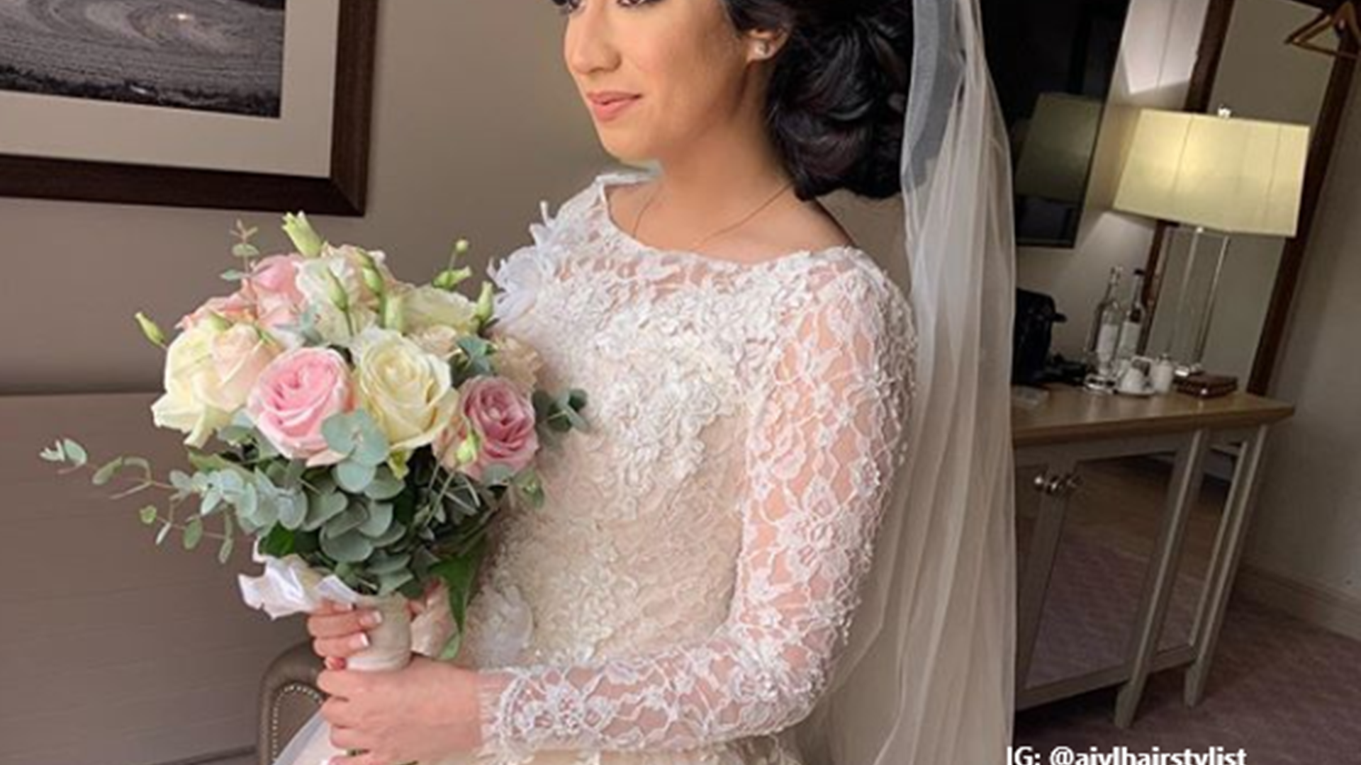 Woman in a white bridal gown and veil holding a bunch of roses on her wedding day