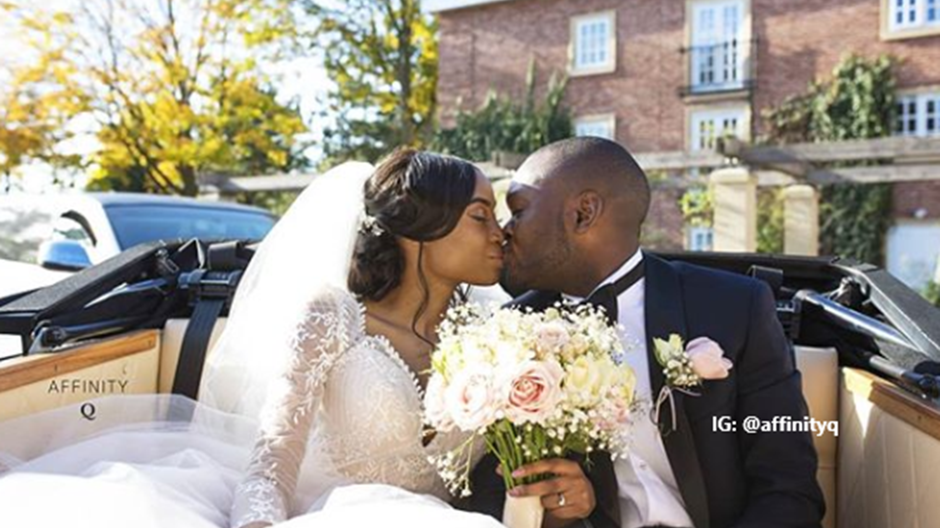 Newly married black couple sitting kissing in the back of traditional wedding car at the Belfry Hotel