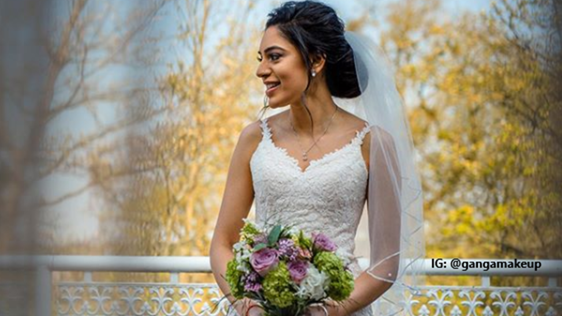Bride with her hair and make up done is standing on a white balcony in front of trees in her wedding dress and veil and holding her bouquet of flowers