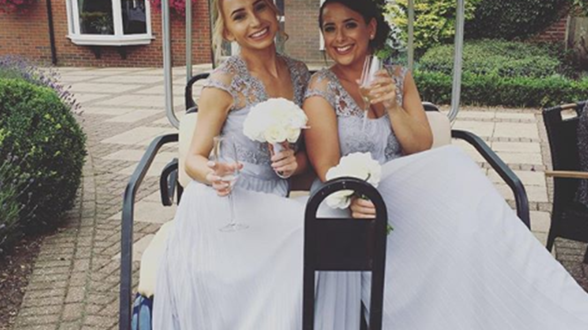 Two Bridesmaids posing and celebrating with champagne in a golf cart