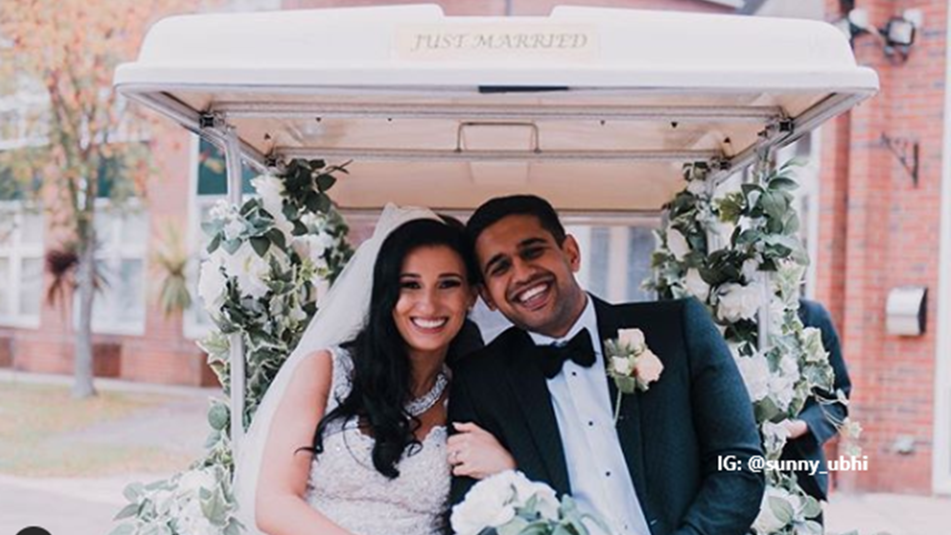 Newly married couple sitting and smiling on the back of a 'just married' golf cart