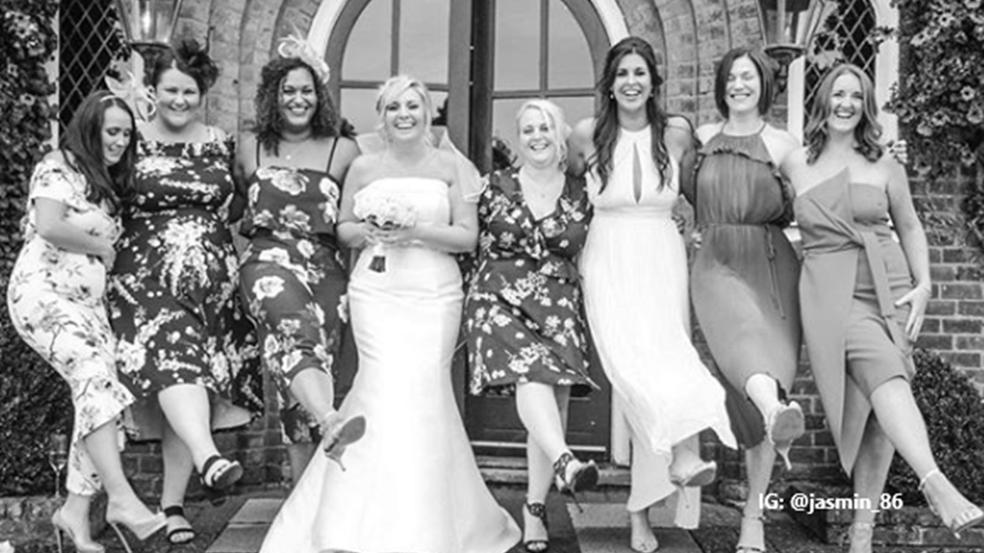 Black and white photo of a bride posing with her bridesmaid and female members of the wedding party