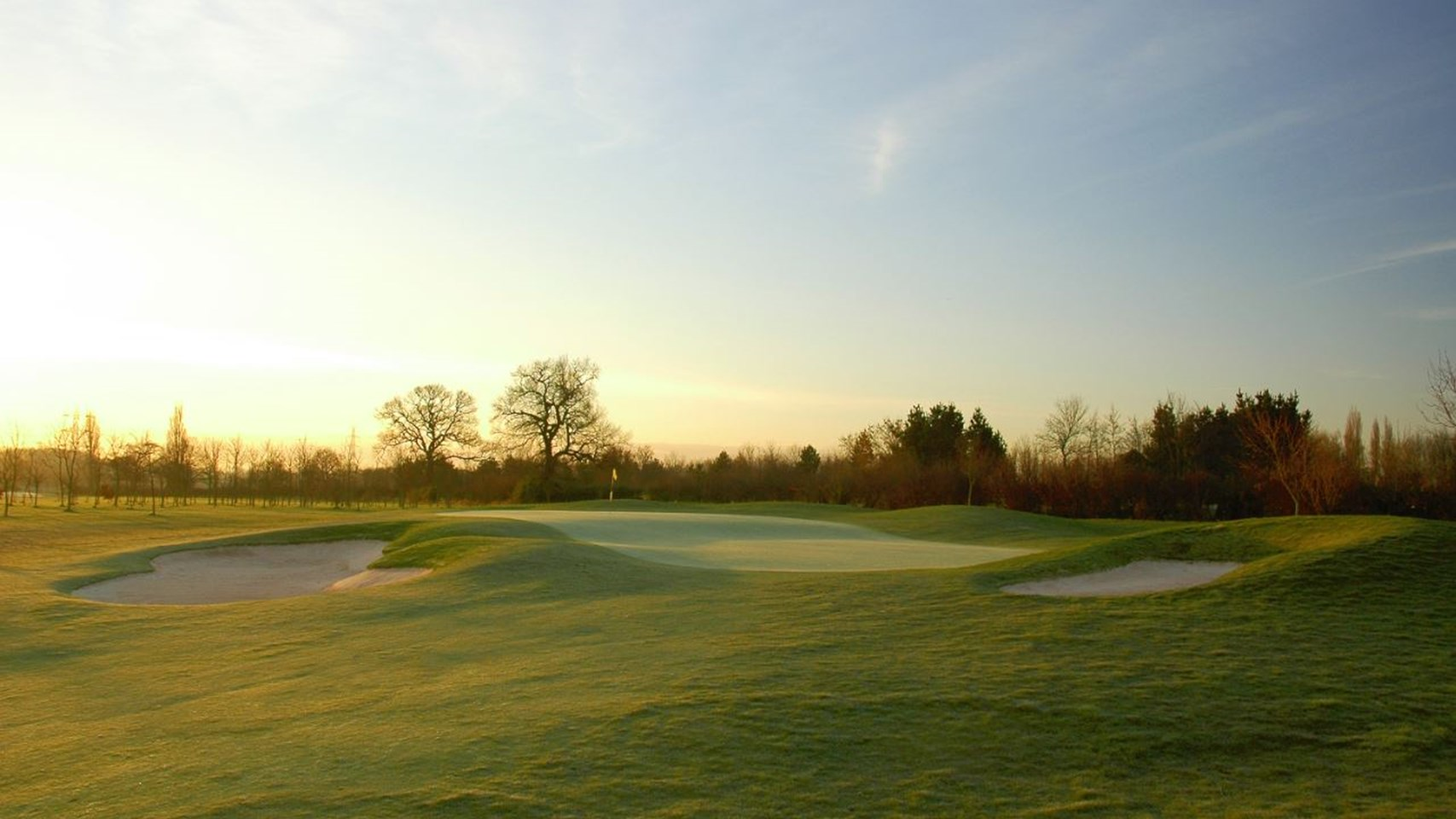 Landscape shot of the bunkers on The Belfry Golf Course with trees in the background on a wintry morning as the sun is rising.